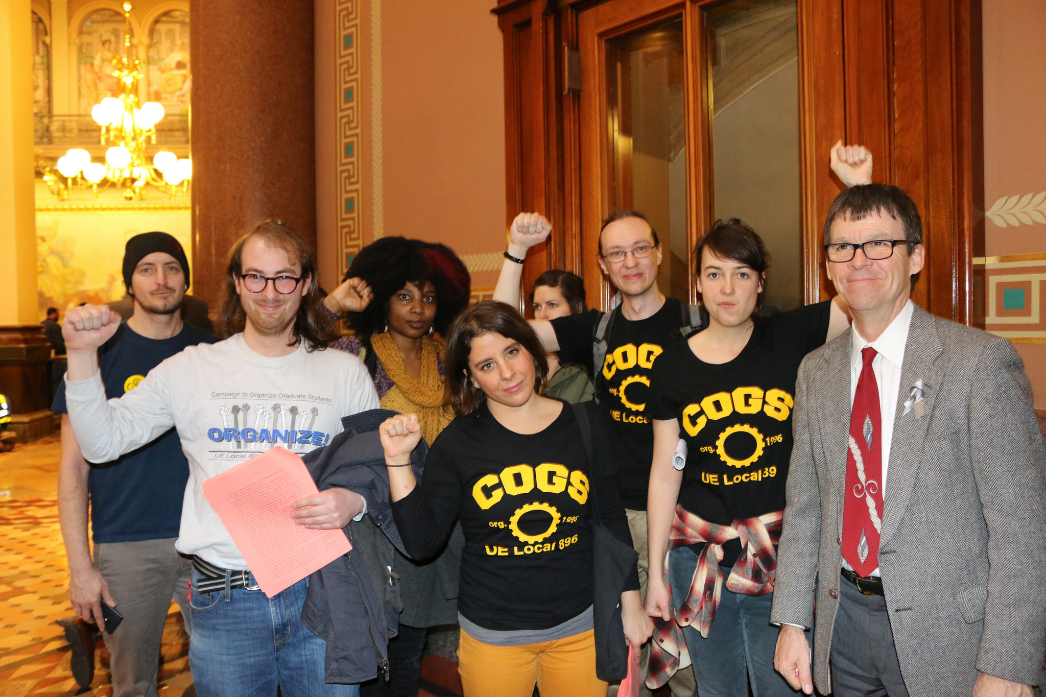 UE Local 896-COGS members in the Iowa state capitol building, with raised fists
