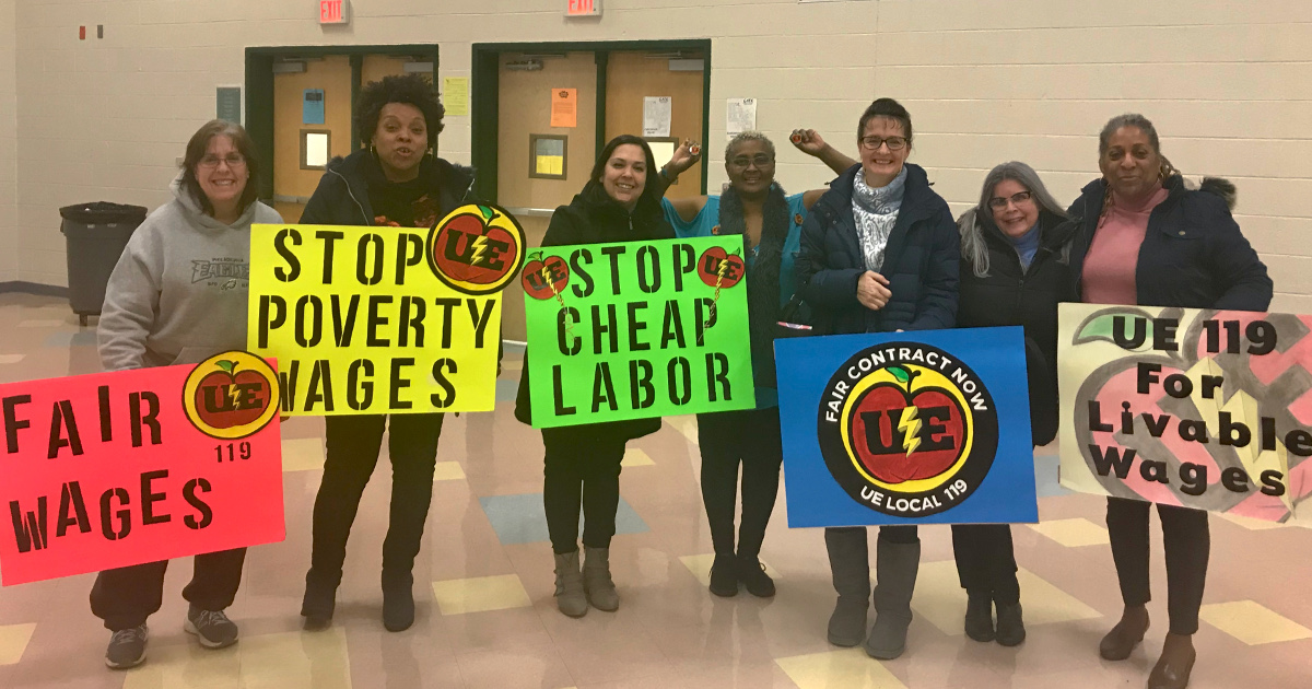 Paraprofessionals in a school gym holding signs demanding fair wages