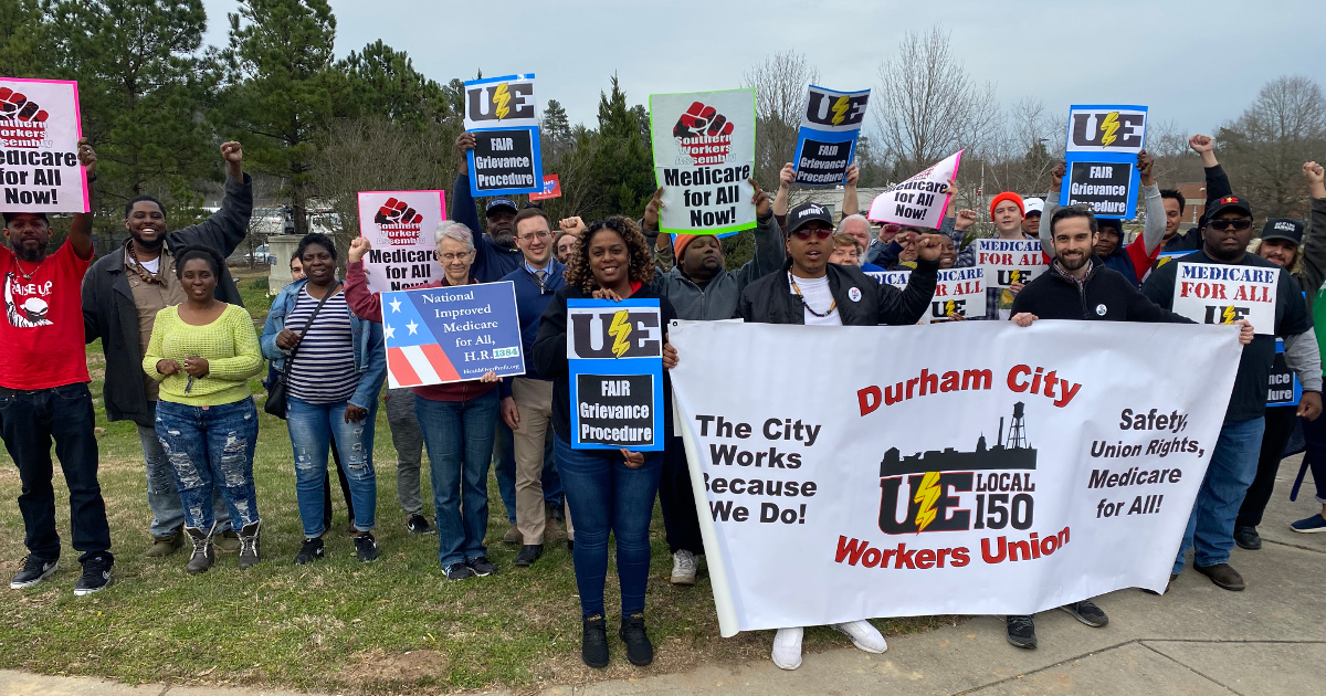 Racially diverse group of workers with a Durham City Workers Union banner and signs demanding Medicare for All and a fair grievance procedure