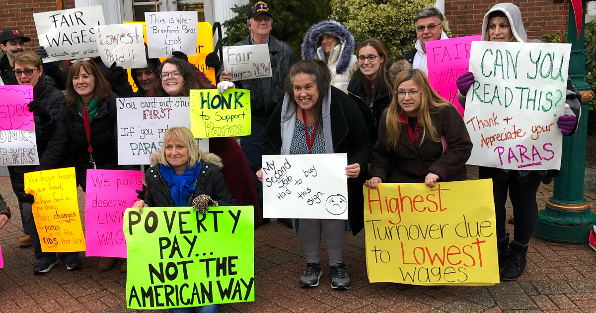 Paraprofessionals holding signs denouncing poverty wages
