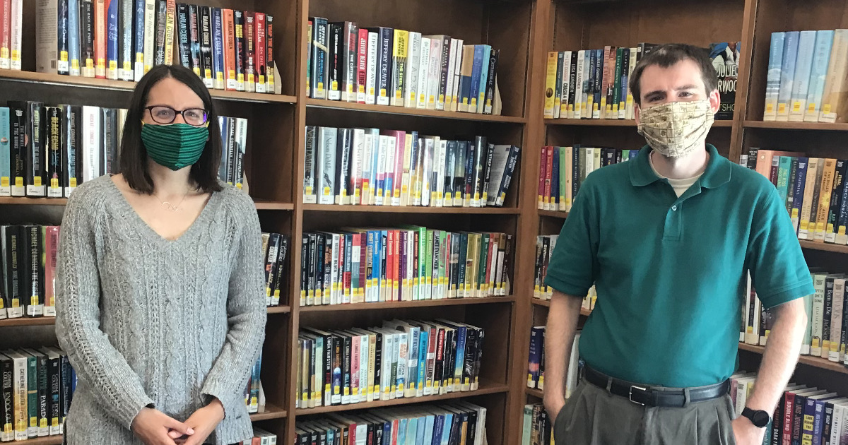 Woman and a man in masks standing several feet apart in front of library bookshelves