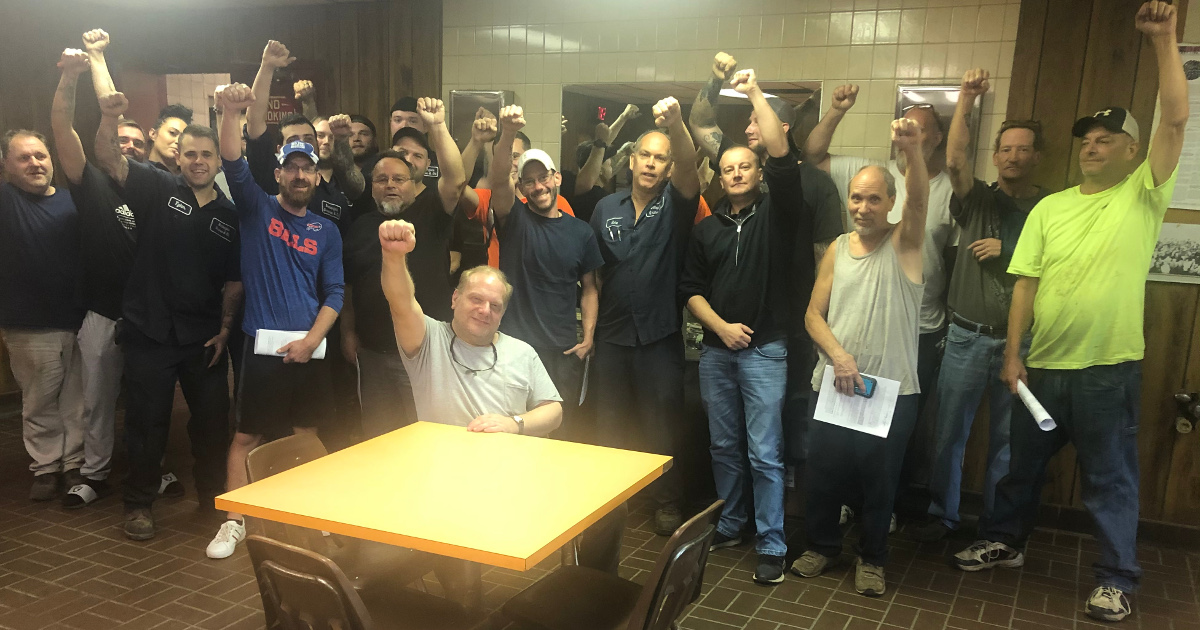 A group of several dozen workers with their fists raised