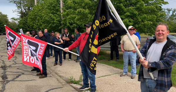 Photo of UE members with flags holding an informational picket at Wabtec's Erie, PA facility
