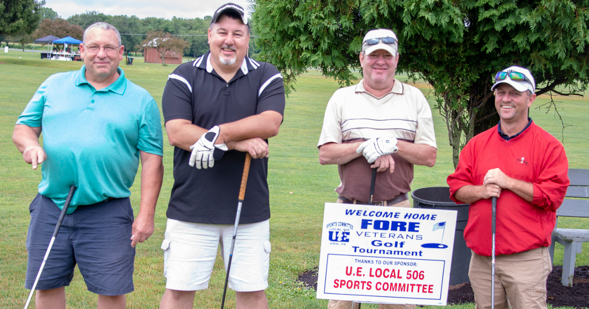 "Four UE members with golf clubs and sign reading ""Welcome home FORE Veterans Golf Tournament - thanks to our sponsor U.E. Local 506 Sports Committee"""