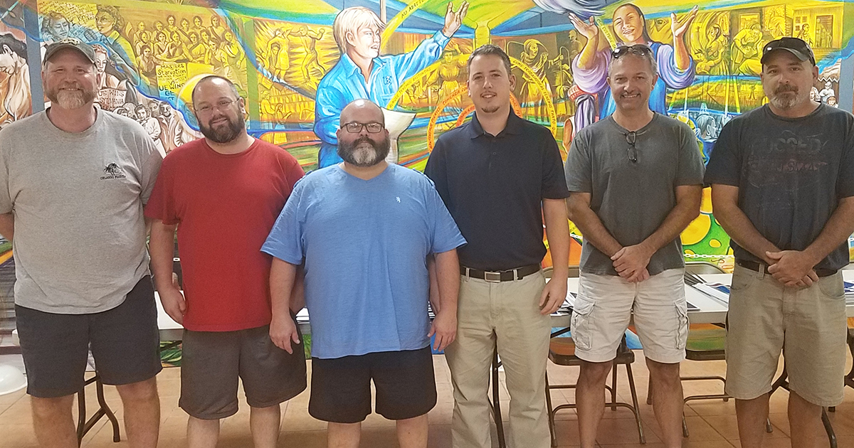 Local 684 negotiating committee members posing in front of a mural