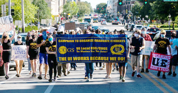 Graduate workers wearing COGS t-shirts and carrying UE Local 896-Campaign to Organize Graduate Students banner