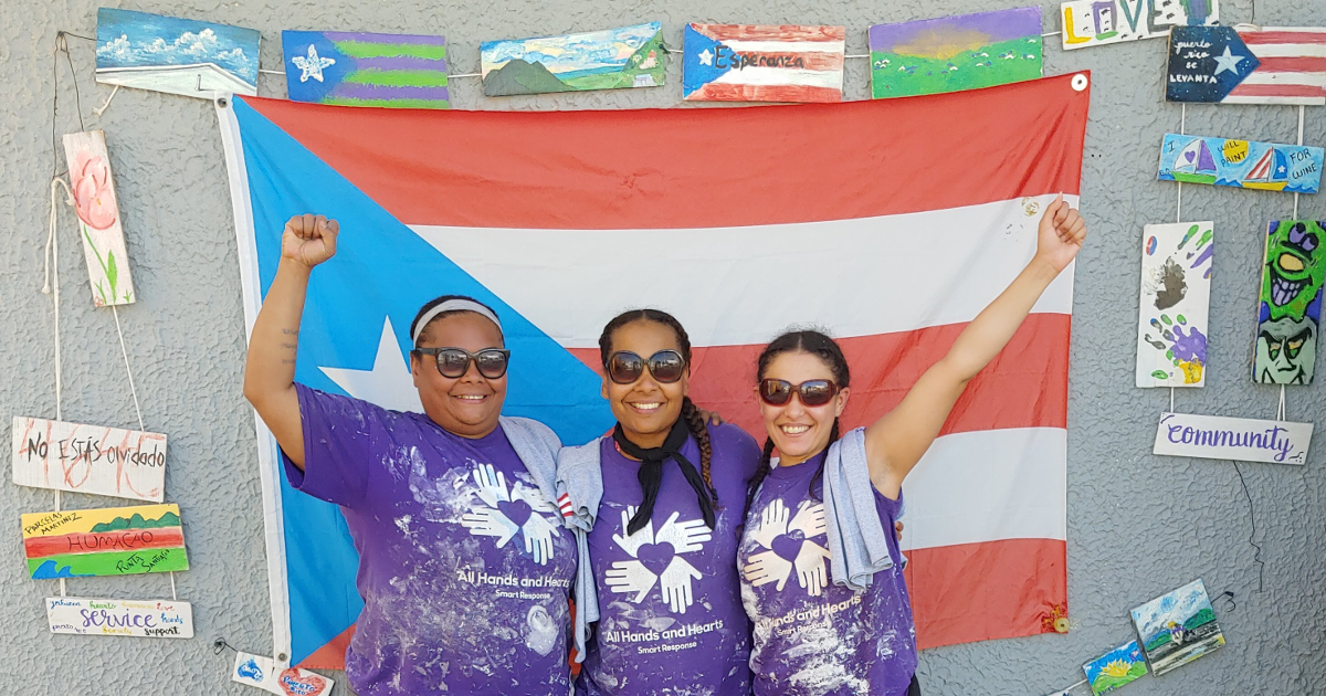 "Three women in front of a Puerto Rican flag with raised fists and wearing purple t-shirts with a logo of four hands and the text ""All Hands and Hearts Smart Response"""