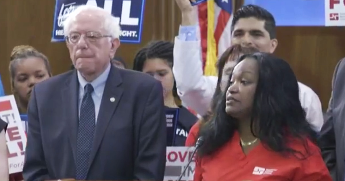 Photo of Bernie Sanders listening to nurse Renelsa Caudill speaking