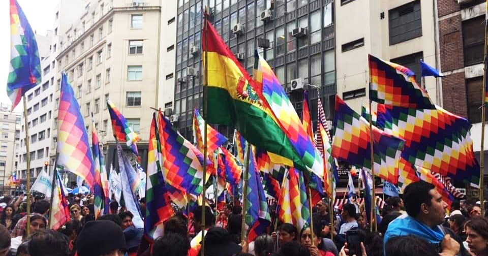 Photo of a Bolivian flag and numerous Pachamama flags
