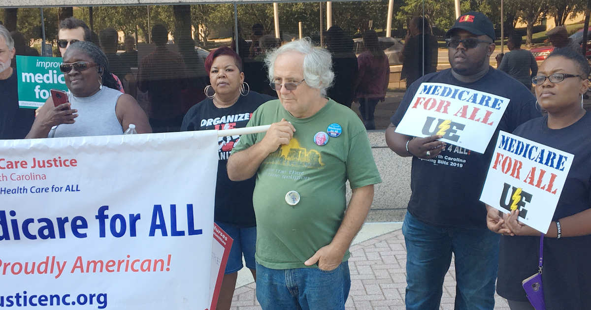 """Picket line with UE members and allies. Two UE members hold signs reading """"Medicare for All"""" with a UE logo."""