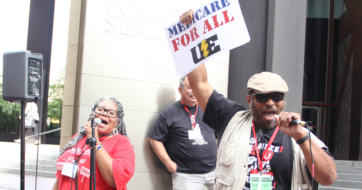 "A woman and a man singing, the man is holding up a sign that says ""Medicare for All"" with a UE logo"