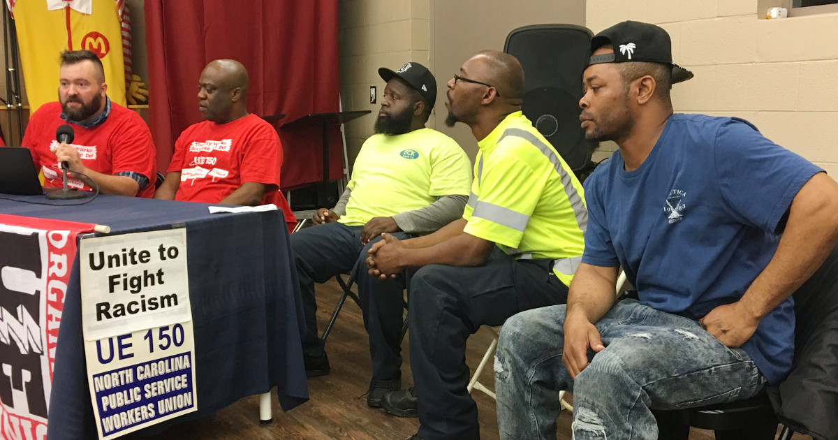 "Five city workers address workers' rights panel. Sign reads ""Unite to Fight Racism - UE150 - North Carolina Public Service Workers Union"""