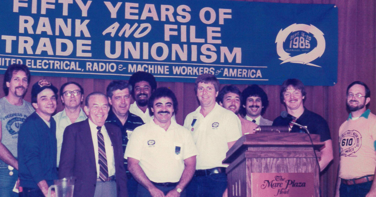 A group of UE members standing on stage under a banner reading Fifty Years of Rank and File Unionism