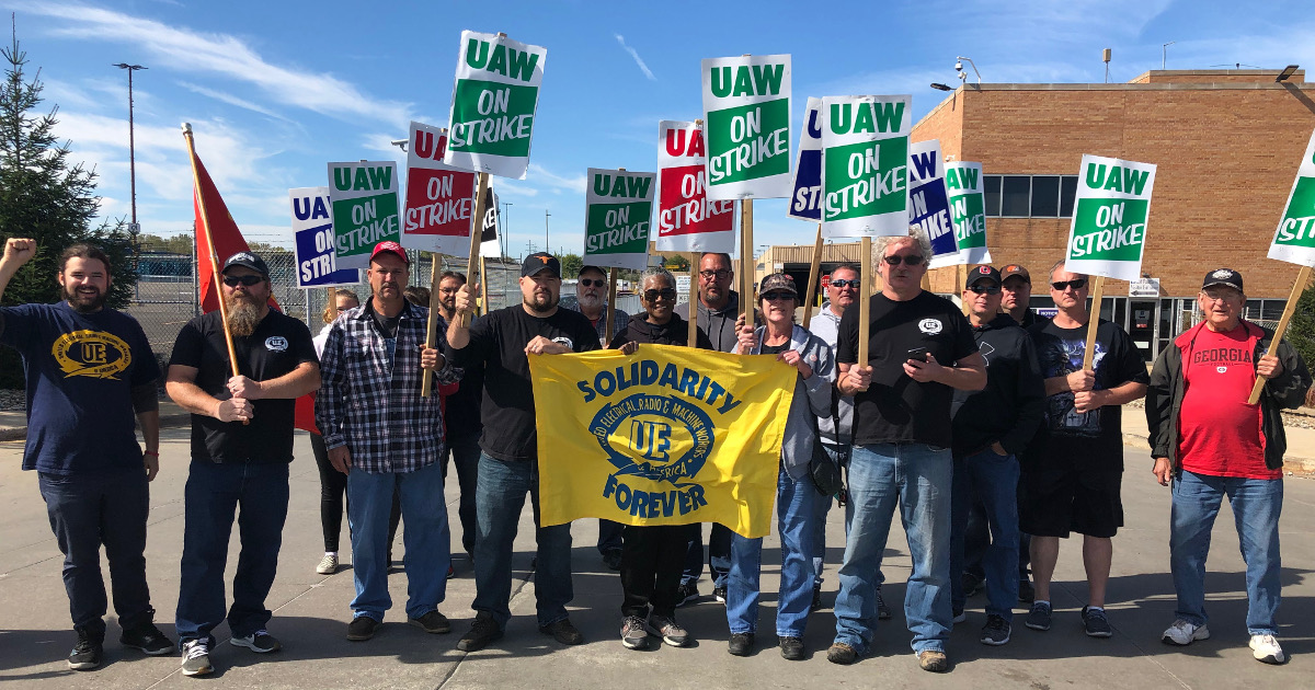 "A group of GM strikers and UE members with UAW On Strike picket signs and a UE ""Solidarity Forever"" banner"