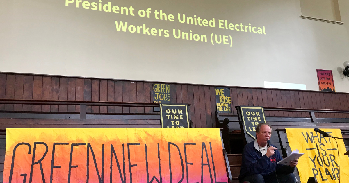"Speaker between banners reading ""Green New Deal"" and ""What is your plan?"" The words ""President of the United Electrical Workers Union (UE)"" are projected above the speaker."