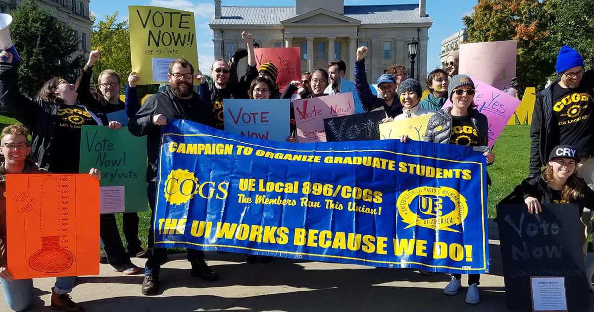 "Members of UE Local 896 with local banner and signs that say ""Vote Now"""