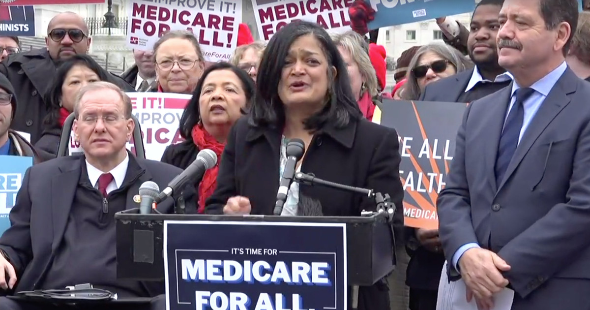 Photo of Rep. Jayapal speaking at a podium surrounded by supporters with Medicare for All signs