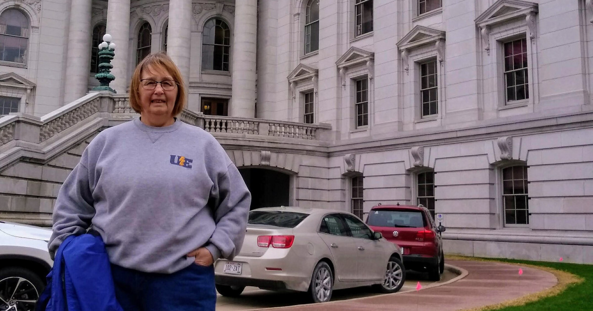 Joni Anderson wearing a UE sweatshirt in front of the Wisconsin state capitol building