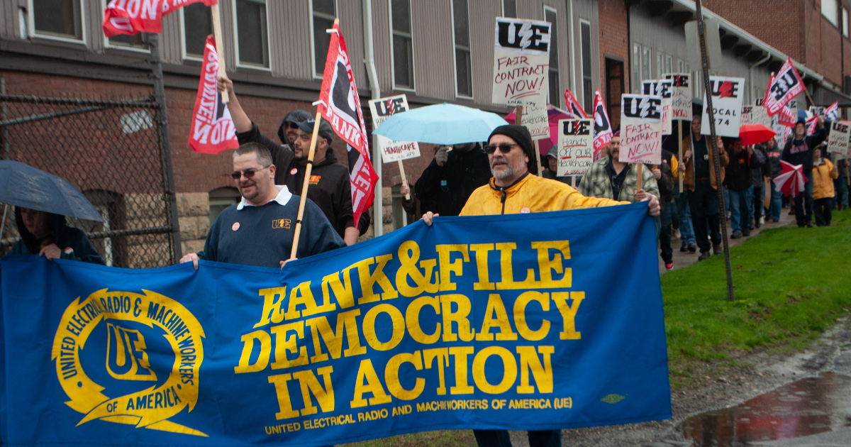 "Picketing/march being led by a banner that says ""UE : Rank & File Democracy in Action"""