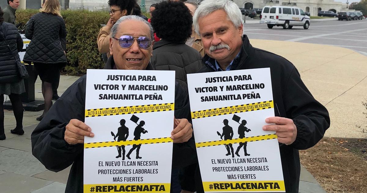 """Two men holding signs that read """"Justicia para Victor Y Marcelino Sahuanitla Peña. El nuevo TLCAN necesita protecciones laborales más fuertes #ReplaceNAFTA"""""""