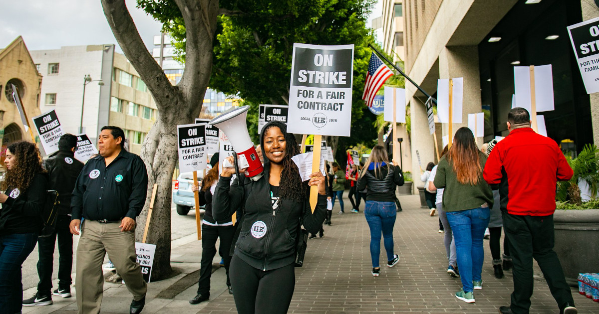 "Photo of woman with megaphone and ""On strike for a fair contract"" sign in front of picketers"