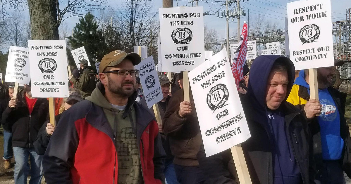"""UE members picketing with signs reading """"Fighting for the jobs our communities deserve"""" and """"Respect our work — respect our community"""""""