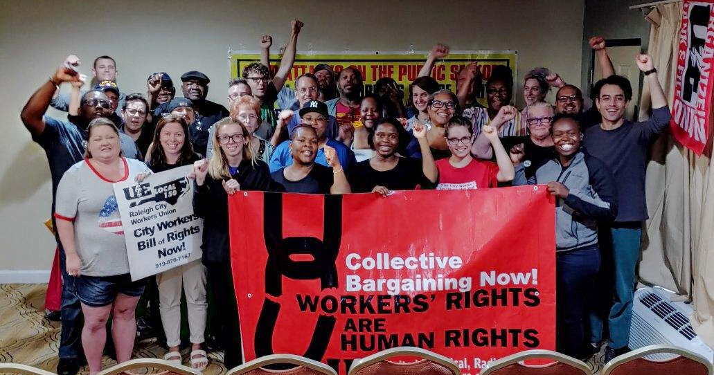 "Group of union members with raised fists and banner reading ""Collective Bargaining Now! Workers' Rights Are Human Rights"""