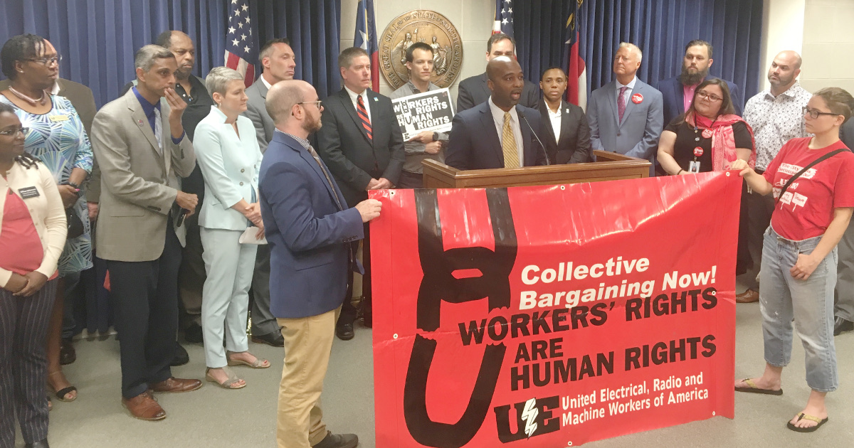 "Rep. Hawkins addressing press conference behind UE banner reading ""Collective Bargaining Now! Workers' Rights are Human Rights"""