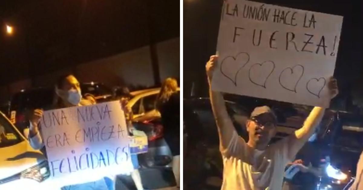 """Workers celebrating with signs reading """"Una nueva era empieza felicidades"""" and """"La unión hace la fuerza"""""""
