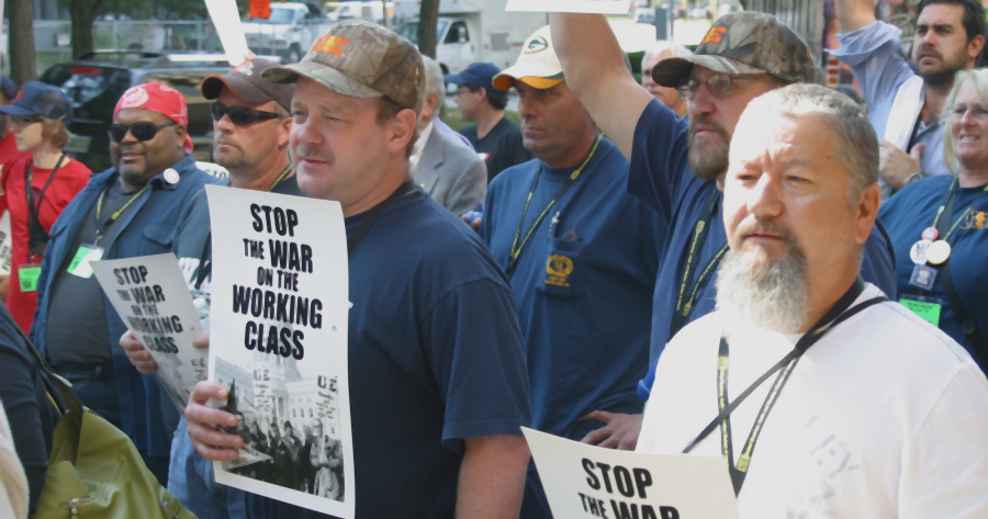 Workers in UE hats and shirts holding signs reading Stop the War on the Working Class