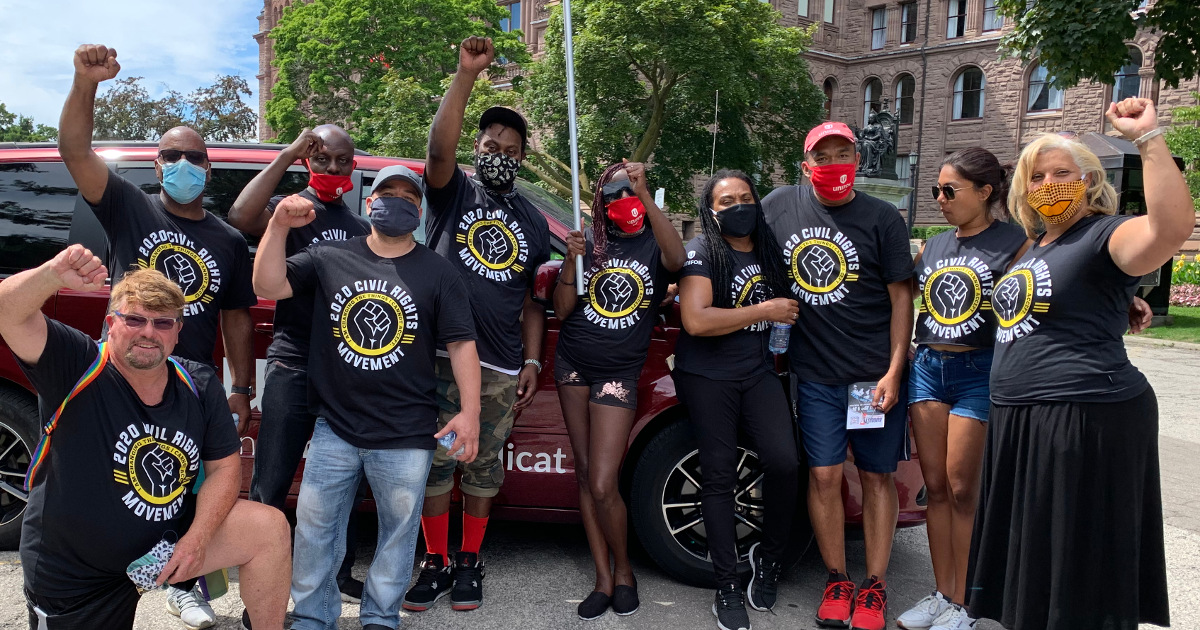 Unifor members with raised fists and shirts reading 2020 Civil Rights Movement