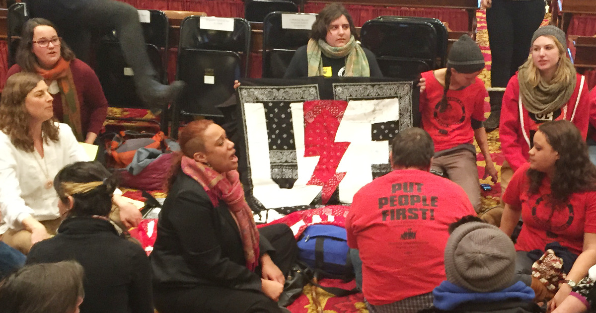 UE members and other protesters in the state legislative chamber with UE banner