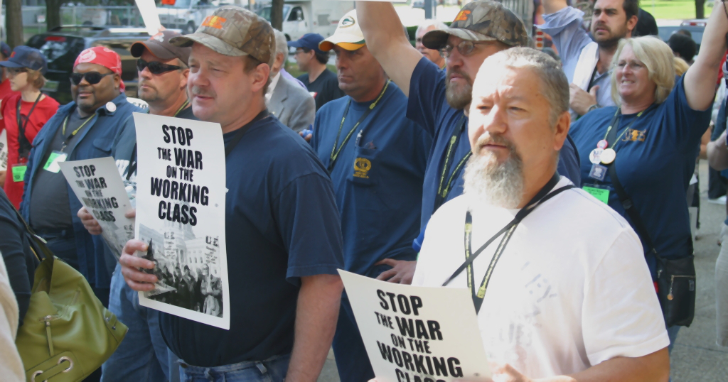 """UE members with signs reading """"Stop the War on the Working Class"""""""