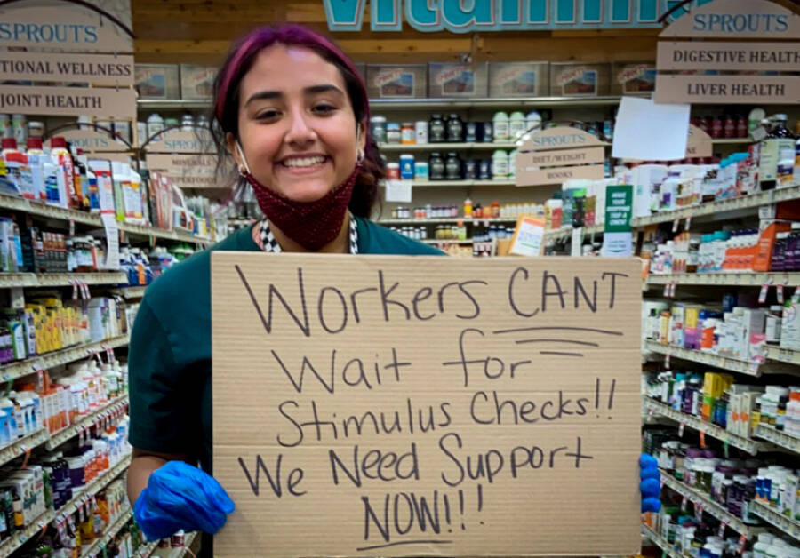 Worker holding sign reading Workers Can't Wait for Stimulus Checks! We Need Support Now!