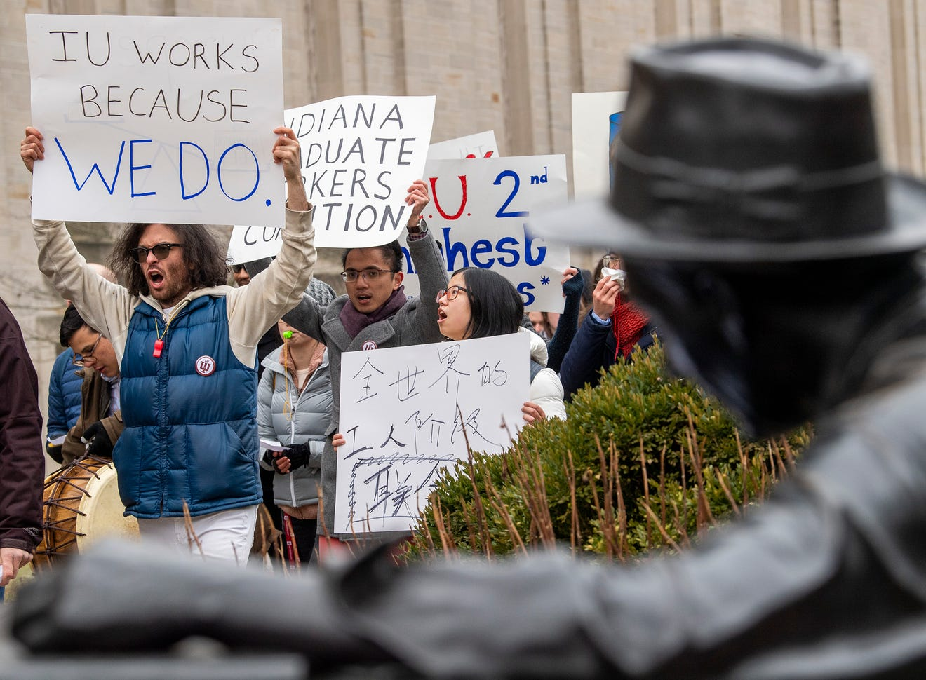 """Alex Goodlad, a member of the Indiana Graduate Workers Coalition, carries a sign reading """"IU works because WE DO."""" towards the Wells Library during a Jan. 28, 2020, protest."""