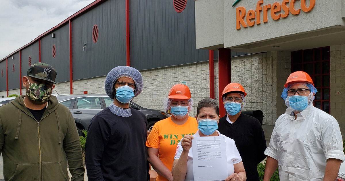 Five workers standing in front of Refreco building with a letter demanding union recognition