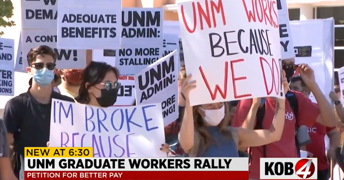 Still image of TV coverage of rally. Title reads UNM Graduate Workers Rally, Petition for Better Pay. Workers holding signs, most prominent one reads UNM Works Because We Do