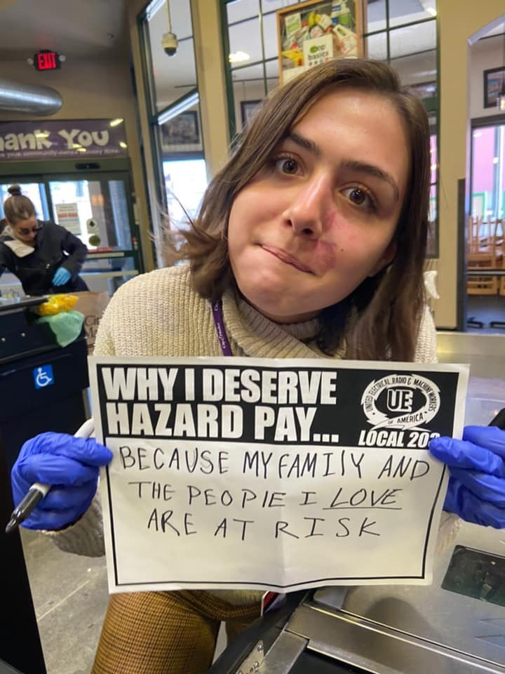 "Women holding a sign saying ""Why I Deserve Hazard Pay... Because my family and the people I love are at risk"""