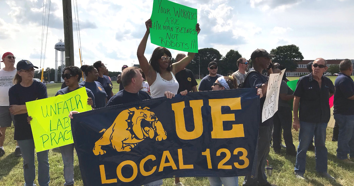 Local 123 members rally in front of the plant with a sign that says Your Workers Are Human Beings Not Robots