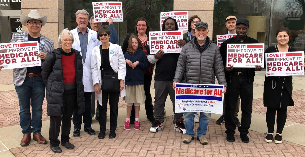 Racially diverse group of men and women with Love It! Improve It! Medicare for All! signs