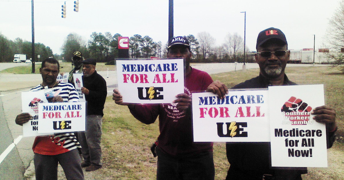A group of Black men holding signs demanding Medicare for All