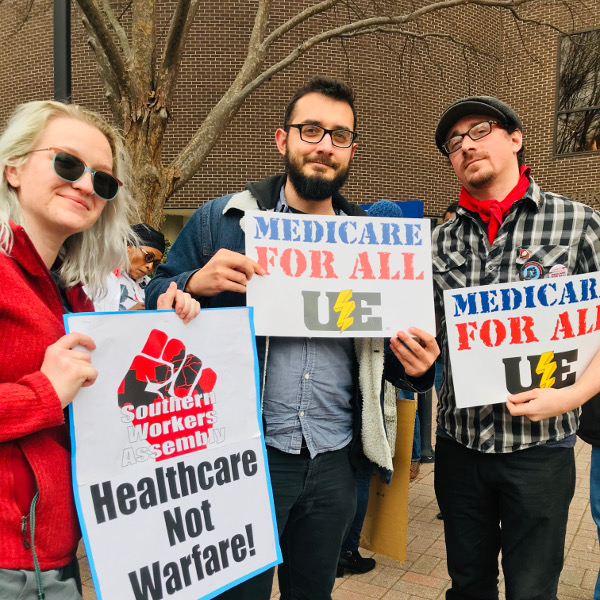Young woman with Southern Workers Assembly Healthcare Not Warfare sign and two young men with Medicare for All UE signs