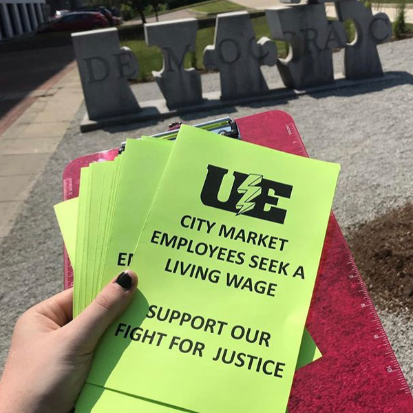 "Union leaflets with a UE logo and the text ""City Market employees seek a living wage. Support our fight for justice."" Behind the leaflets is a sculpture of puzzle pieces that spell out the word ""democracy."""