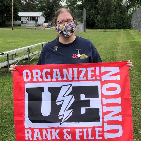 "UE member in a mask with a red UE flag with the words ""Organize! Rank & File Union"""