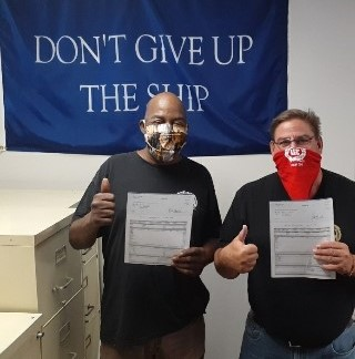 Two men wearing masks with thumbs up, standing in front of a banner reading Don't Give Up the Ship