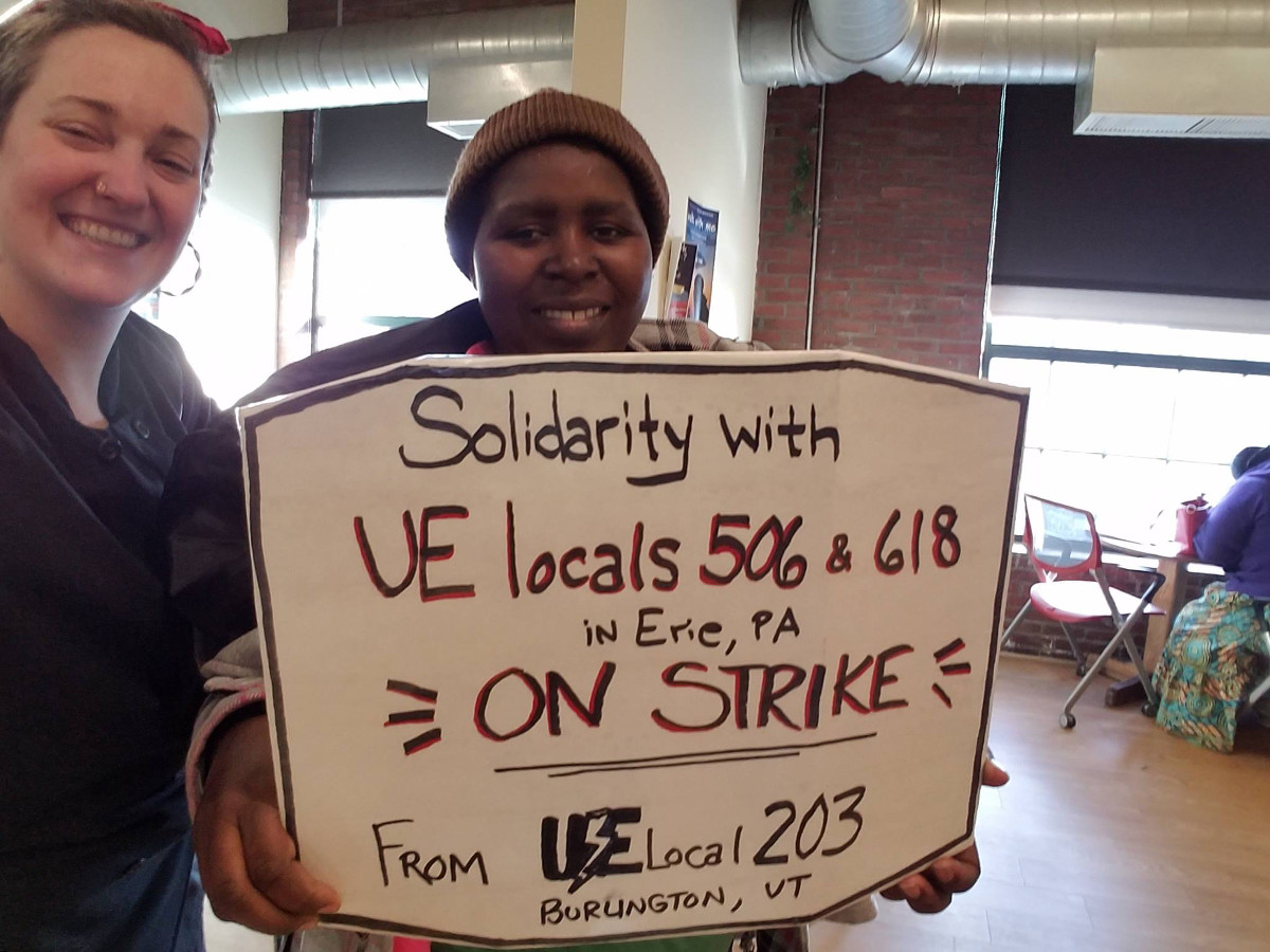 "Two UE members with a sign reading ""solidarity with UE Locals 506 & 618 in Erie, PA on strike from UE Local 203 Burlington, VT"""