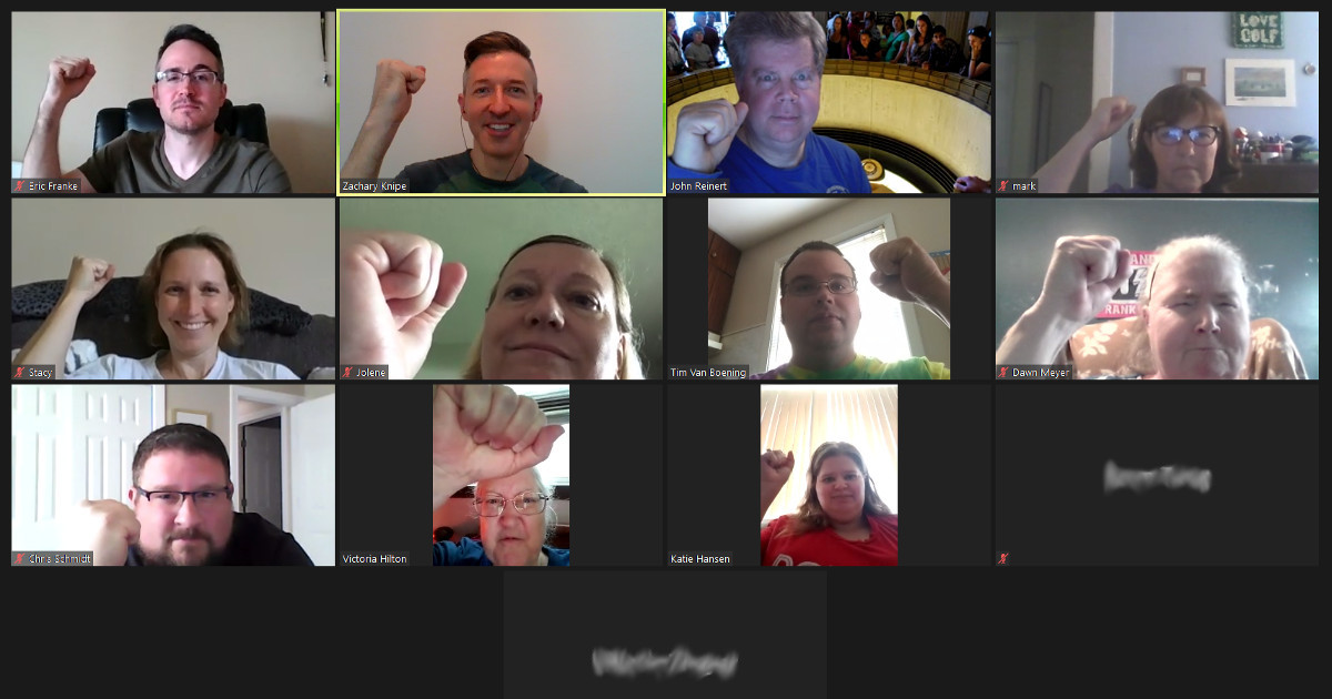 UE Local 808 members raise fists on a Zoom meeting