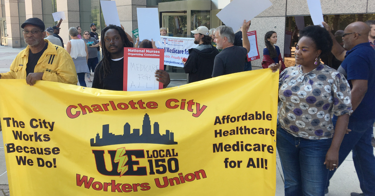 "Two UE members holding a sign reading ""Charlotte City Workers Union, UE Local 150. The City Workers Because We Do! Affordable Healthcare Medicare for All!"""