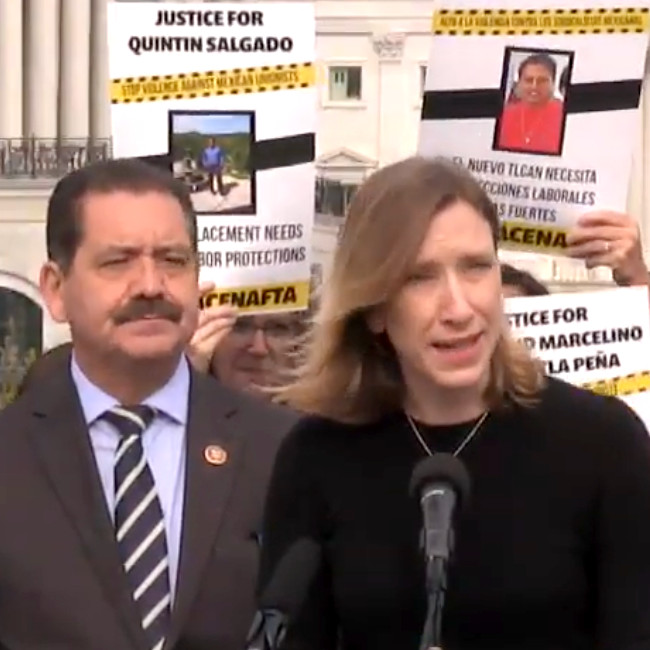 "Sister Quincy Howard speaking into a microphone with Congressman Chuy Garcia next to her and a placard reading ""Justice for Quintin Salgado"" behind them."