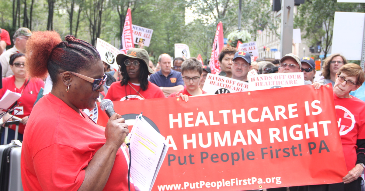 "Frederica Phillips speaks in front of a banner that says ""Healthcare Is a Human Right / Put People First! PA / www.PutPeopleFirstPa.org"""